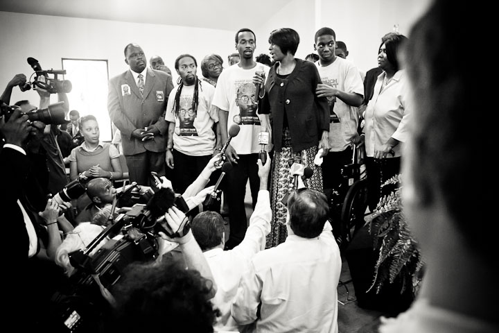 During the press conference, the family of Troy Davis address the media, with Martina Correia, sister of Troy Davis, speaking on their behalf. After her statement, she shares about her declining health that has left her confined to a wheel chair, but, with her strong will, announces she will stand up for her brother - rising from her seat, balanced by her son's hand.